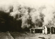 air filled with dust and dirt as it approaching two homes during the Dust bowl in the 1930s.