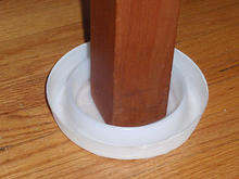 a white plastic dish within a dish under a furniture leg