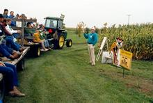 Mark Seeley giving a speech in front of a corn field to an audience on tractor