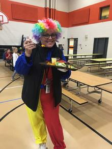 The principal of Menagha elementary wears a silly clown costume and is holding a tray of vegetables in the school cafeteria.