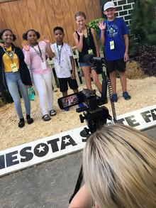 videographer pans across group of five youth in front of Minnesota State Fair sign