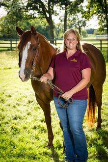 Krishona Martinson standing with and holding reins of brown horse with white face