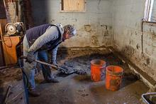 Removing mud from a basement after a flood.