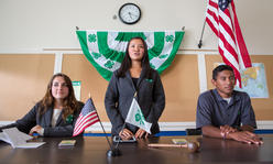 3 teens lead meeting, with flag behind