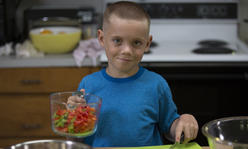 boy at kitchen table with bowl of strawberries