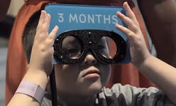 Boy tryign on goggles to see what a 3 month old sees