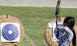 girl aims her bow and arrow at a target