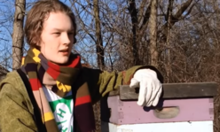 youth holding top of beehive box