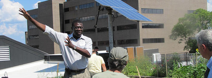 Roof top garden with solar panel and tall buildings in background with a man with his arms in the air as he talks to other people.