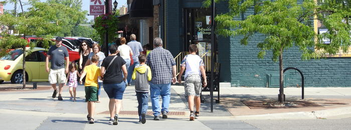 Group of people walking down sidewalk in small town