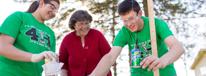 Two 4-H'ers and volunteer working on science experiment