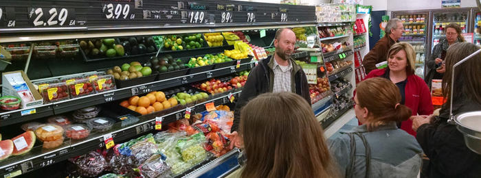 Ryan Pesch standing in front of a rural grocery store produce cooling talking to class attendees about proper produce handling.