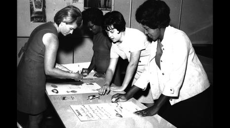 historical black and white photo of 4 nutrition educators making a poster in the 1960s