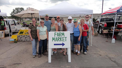 Group of people standing together behind a Farm Market sign. Farmers' market booths set up behind the group.
