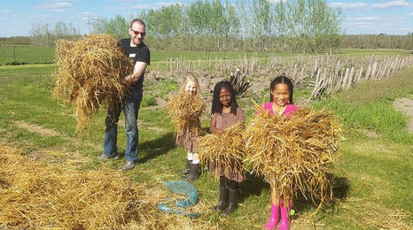 Children and an adult carrying bundles of loose straw for community garden.