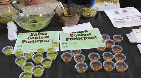Table with small containers with samples of salsa for a competition.