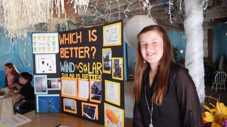 A student standing next to a table presentation about wind and solar.