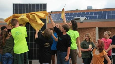 A group of student cutting a yellow ribbon from a new solar panel.
