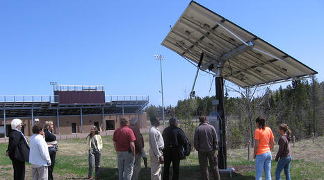 Group of people looking at an elevated solar panel.