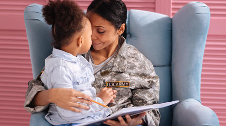 Army mother reading to her daughter while sitting on a chair.