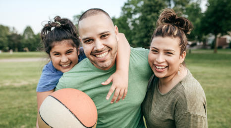 Father and daughters playing basketball