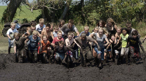 Residents participating in a muddy community event