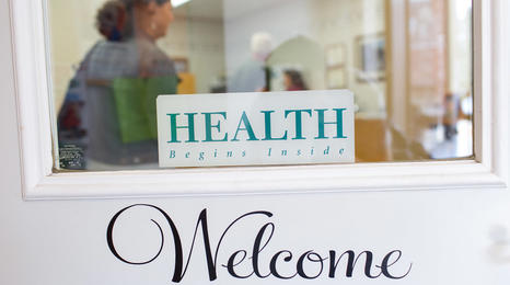 A welcome sign on the entry door to a health clinic