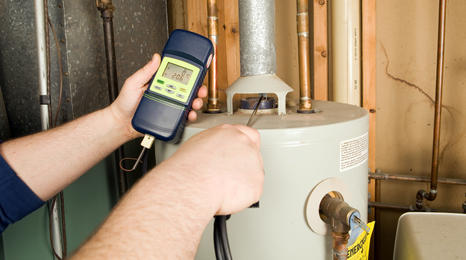man using a digial device to take the reading on a water heater