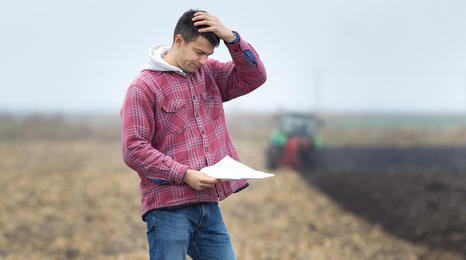 Worried farmer looking at a document