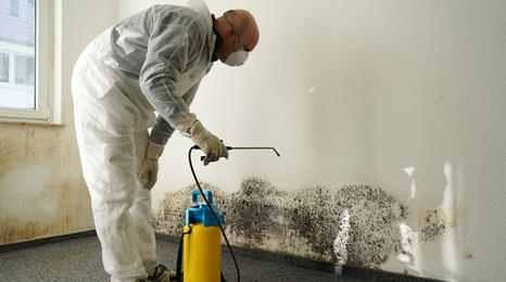 man in protective gear spraying chemicals on the inside of a building