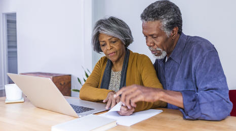 an older woman and man reviewing some paperwork in front of a laptop computer