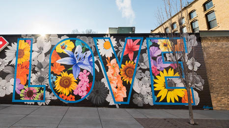 A mural of flowers with the word love in big letters on a building in Northfield, Minn.