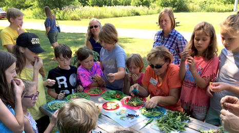 children gathered around a picnic table outside with adults helping prepare vegetables