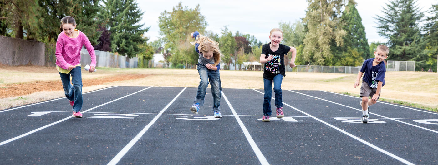 4 kids running on a track