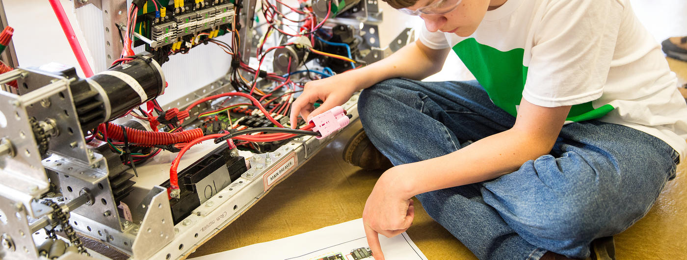 boy examines inside of a computer