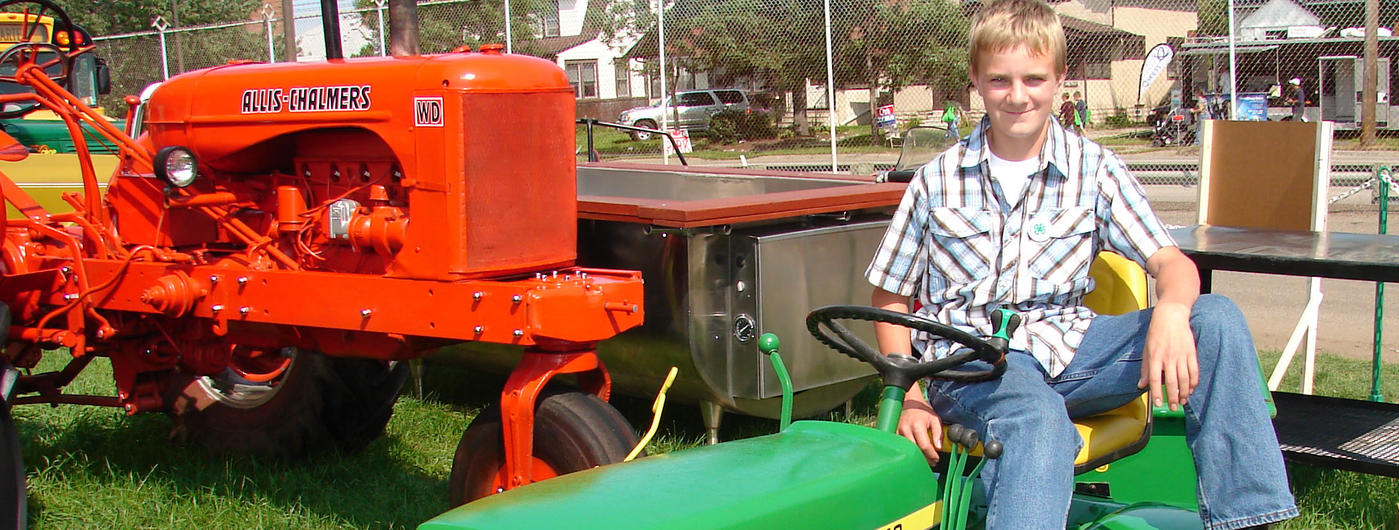 boy with Allis Chalmers and John Deere tractors