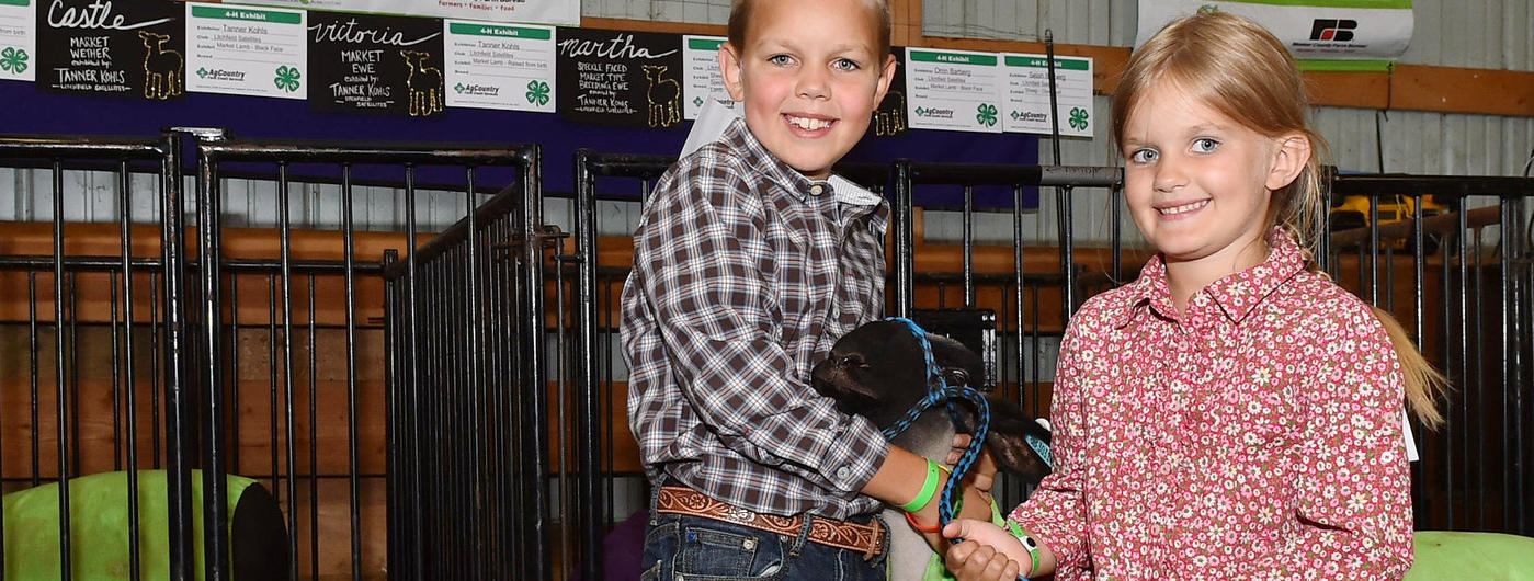 Young boy and girl with a lamb in front of county fair sheep pens