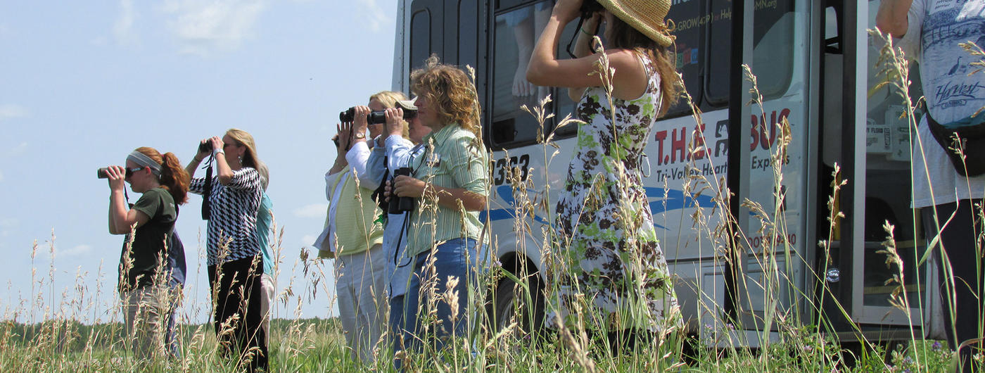 Group of people standing if field holding binoculars to face birding watching.