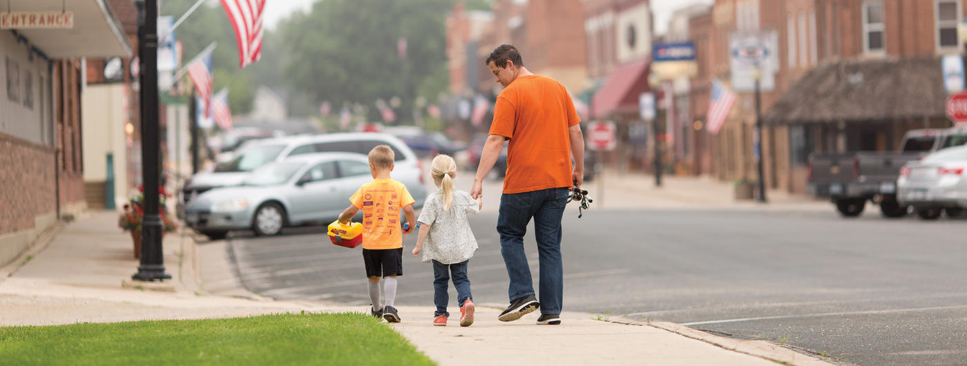 Father and children walking down a street