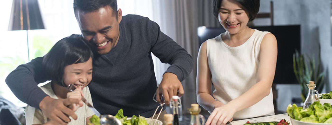 Asian American family of three cooking together