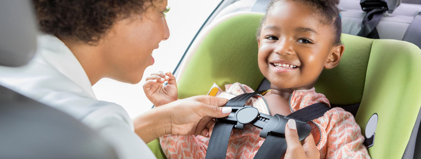 Mother buckling child into car seat