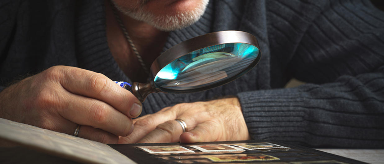 Man looking at pictures with magnifying glass