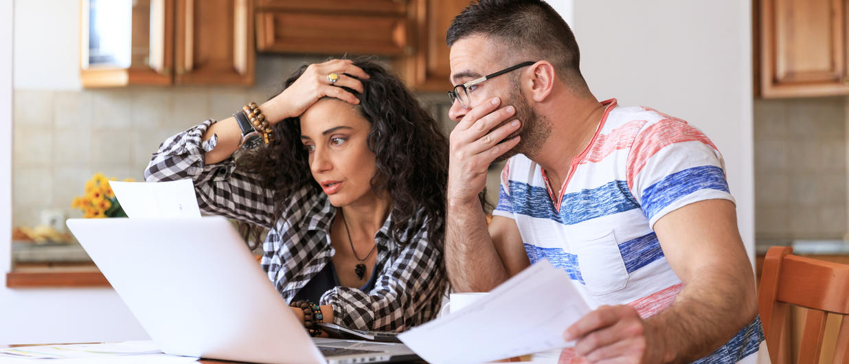 woman and man looking at some paperwork, appearing upset