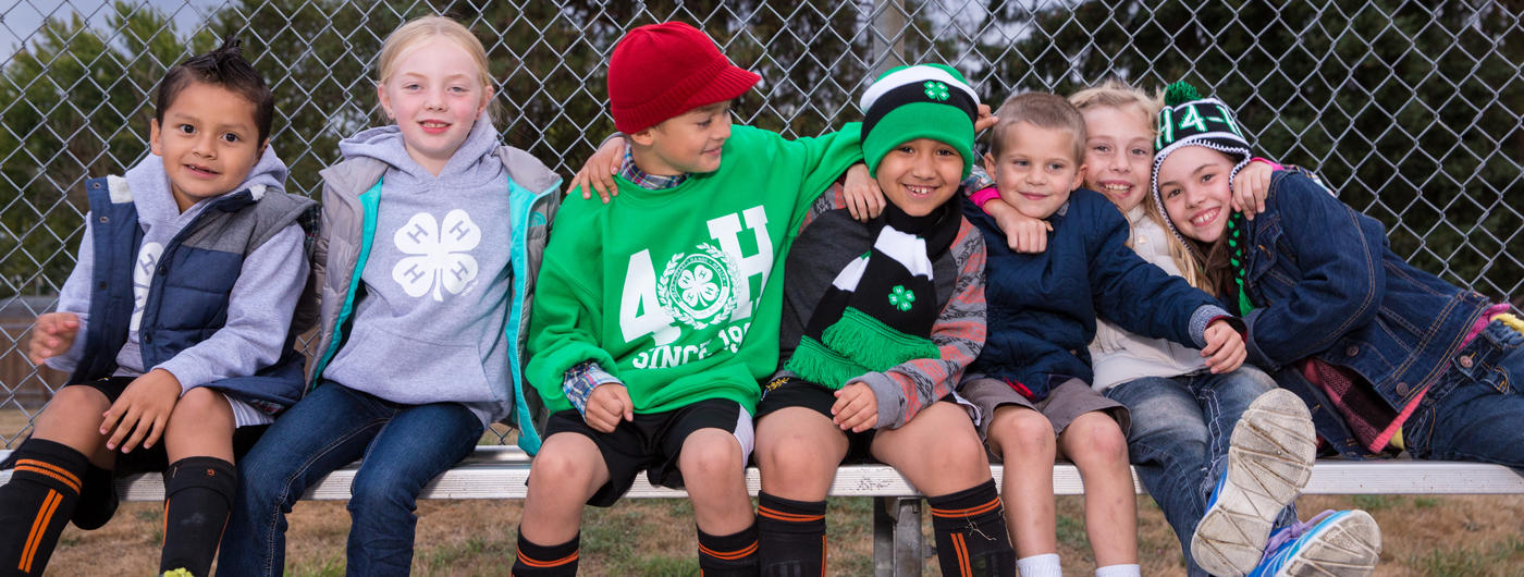 Group of kids in 4-H attire sitting on a bench.