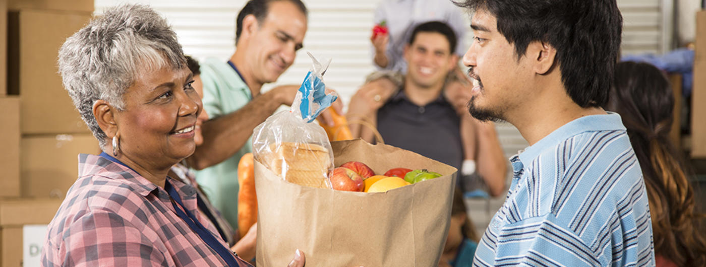 Woman giving food to young man at food shelf
