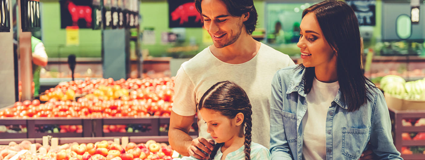Family of three shopping in produce aisle