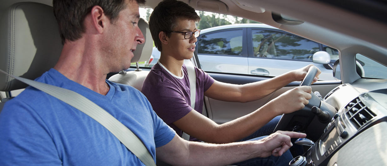 Father teaching son to drive