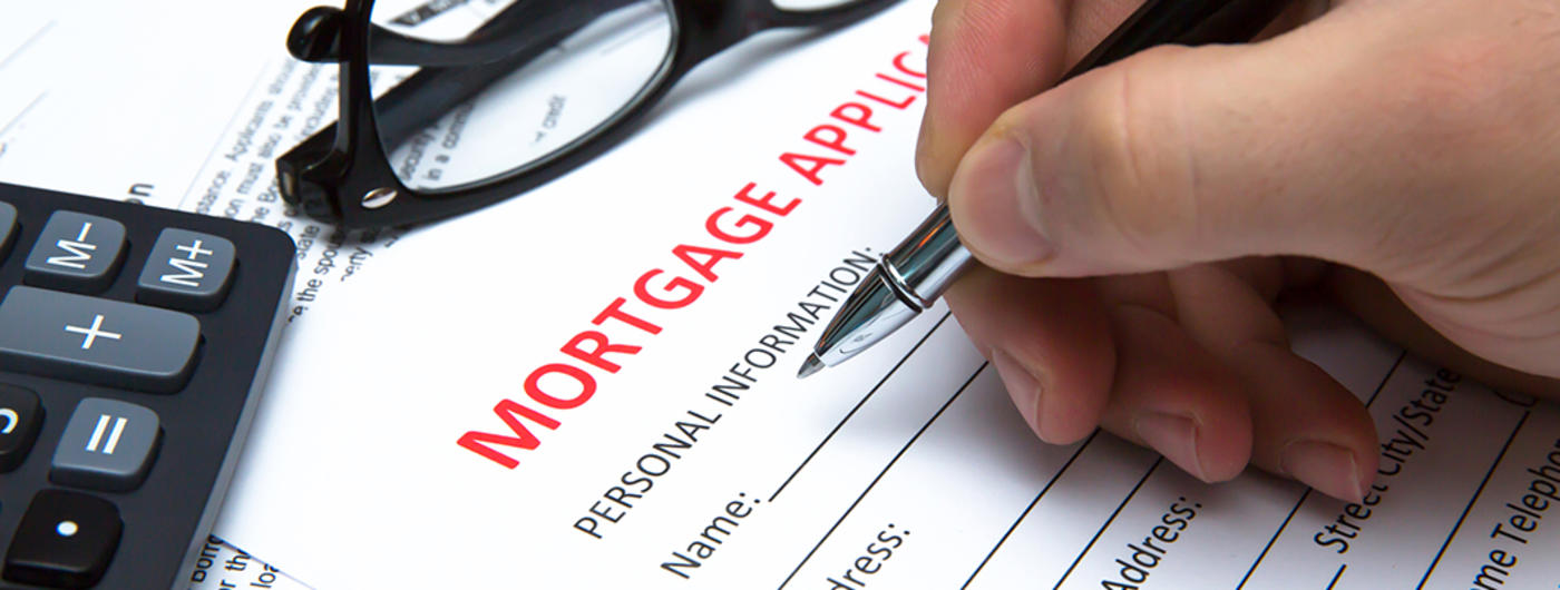hand completing a mortgage application