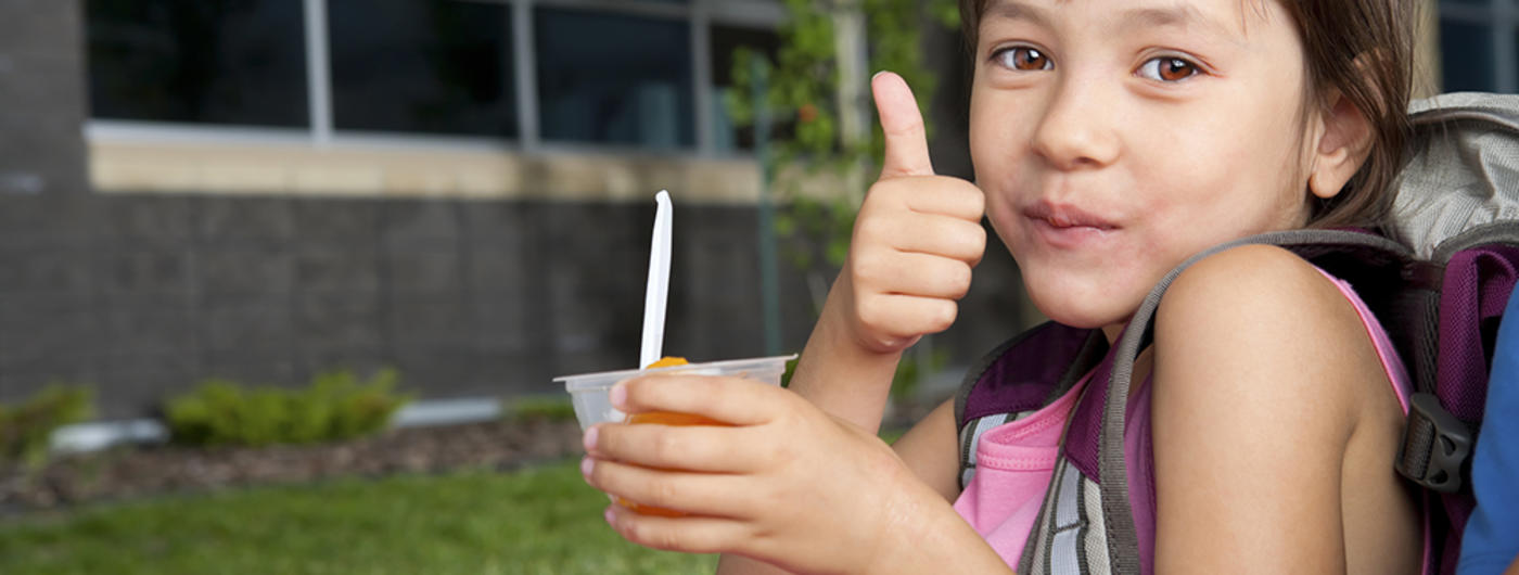 Young girl with backpack eating out of fruit cup and giving thumbs up
