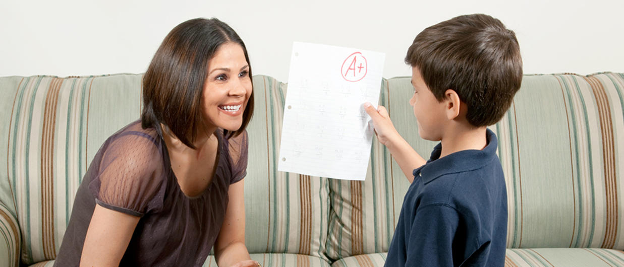 Young son showing mother report card